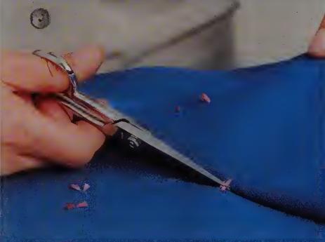 Pull the fabrics apart and clip the tacks